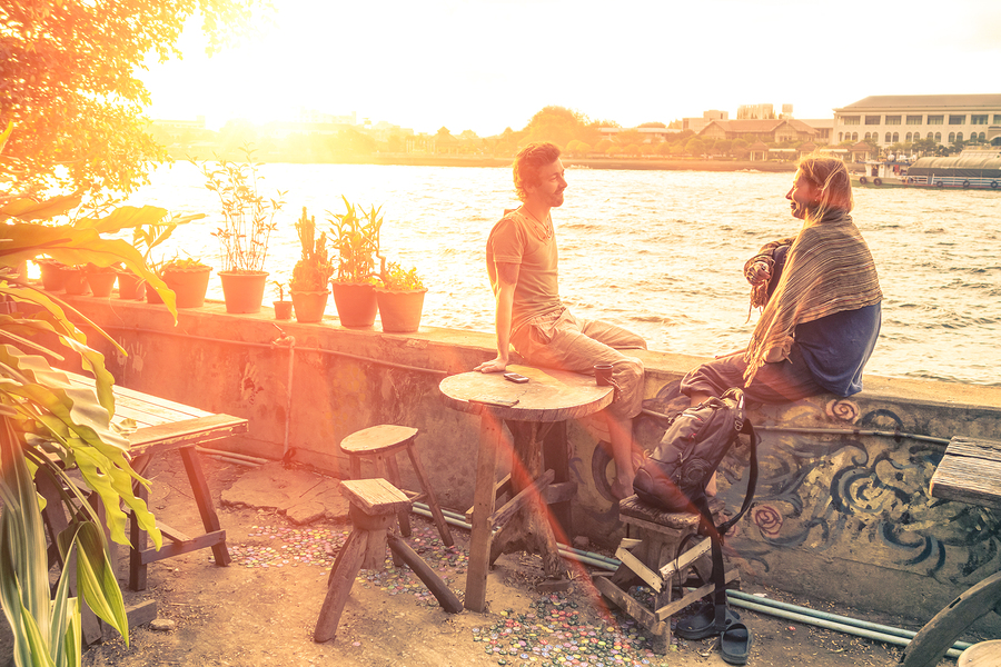 Couple of best friends travelers talking at sunset - Travel concept around the world with exclusive destinations - Young hipster wanderers relaxing and enjoying alternative holidays life experiences
