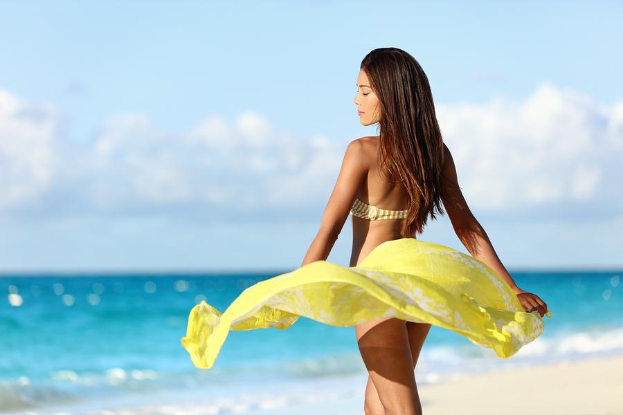 Carefree beautiful sexy bikini body woman relaxing in yellow flo