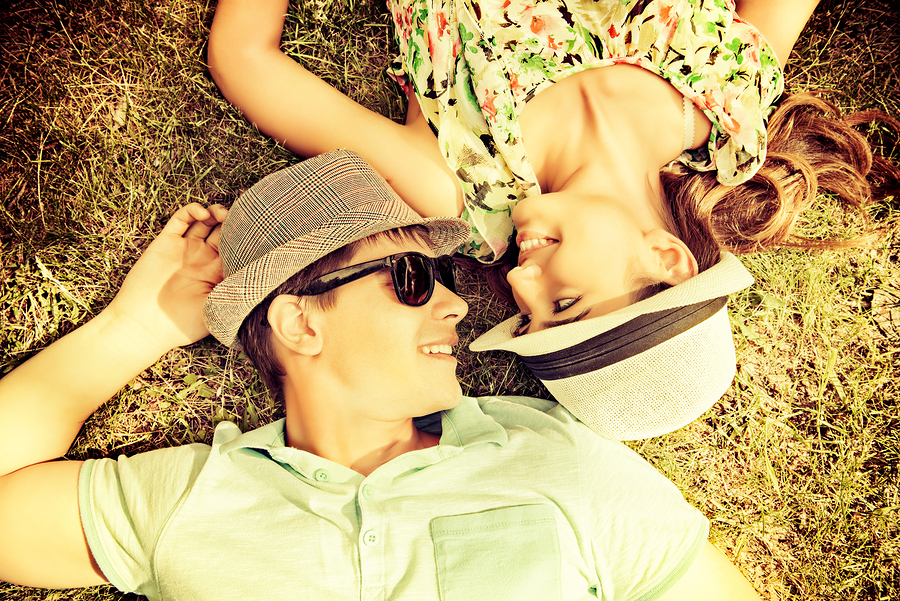 Happy young couple relaxing on the lawn in a summer park. Love c