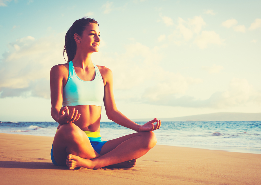 Happy young woman practicing yoga on the beach at sunset. Health