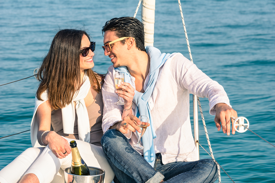Young Couple In Love On Sail Boat With Champagne Flute Glasses -