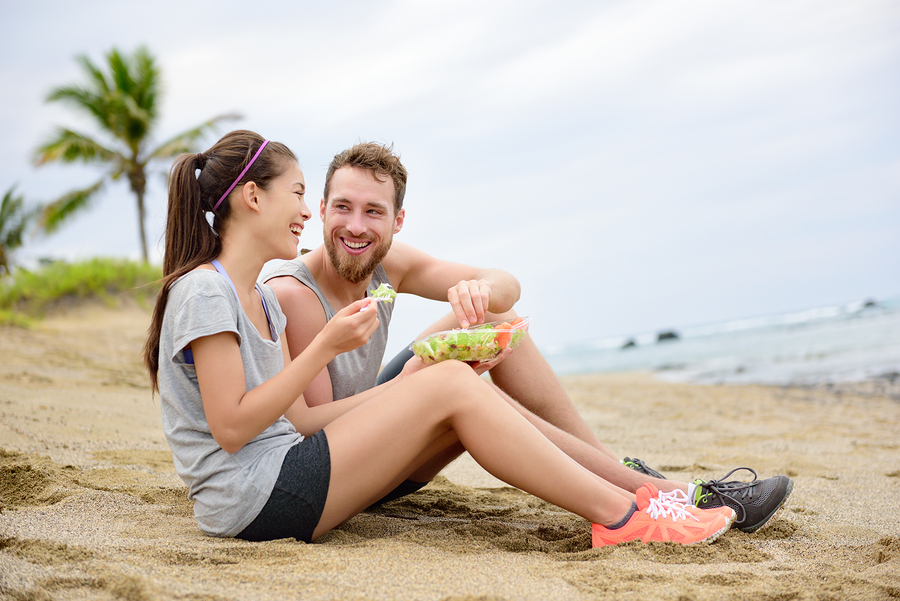 Salad - healthy fitness woman and man couple laughing eating foo